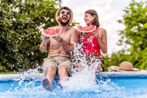 couple eating watermelon by pool